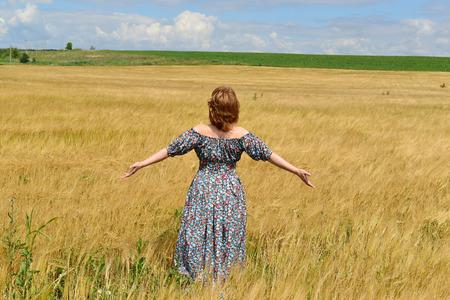 maxi dress: woman in maxi dress standing on the rye field