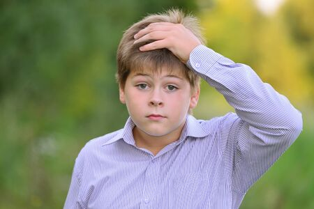 Astonished boy holding his hands behind his head
