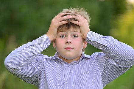 teener: Astonished boy holding his hands behind his head