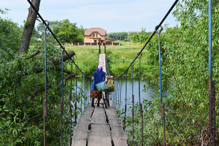 bridging: Grandmother with a bicycle and shopping bags are on the suspension bridge over the river