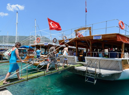to go up: Kemer, Turkey - 06.20.2015. tourists go up the ladder on the boats for excursions in the Mediterranean Sea Editorial