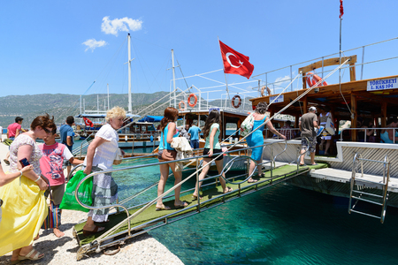excursions: Kemer, Turkey - 06.20.2015. tourists go up the ladder on the boats for excursions in the Mediterranean Sea Editorial