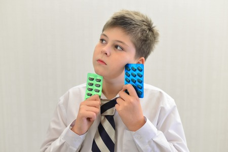 choke: A teenage boy with the medicine in his hands Stock Photo