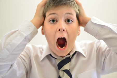 screaming head: Teen boy screaming holding his hands behind his head