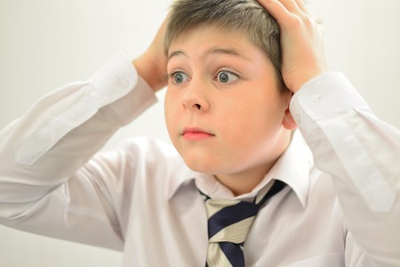 an Astonished boy holding his hands behind his head