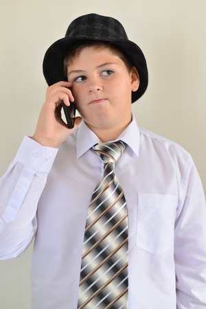 pert: Teen boy talking on cell phone on a light background