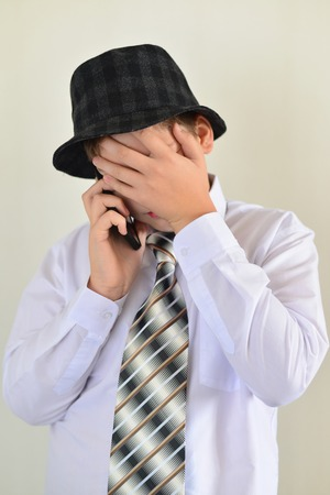 accosting: Teen boy talking on cell phone on a light background