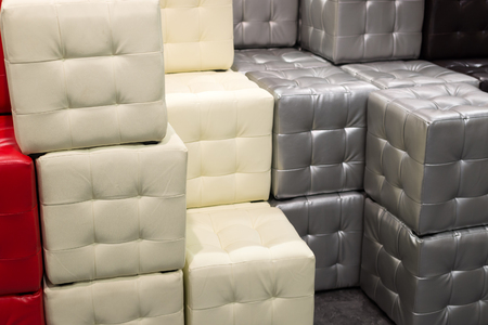 Many leather footstools of different colors in the stack
