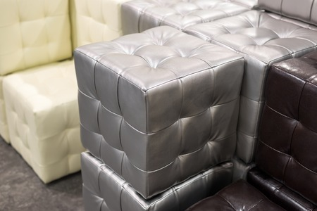 footrest: Many leather footstools of different colors in the stack