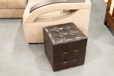footrest: Brown leather ottoman in the interior of the apartment Stock Photo