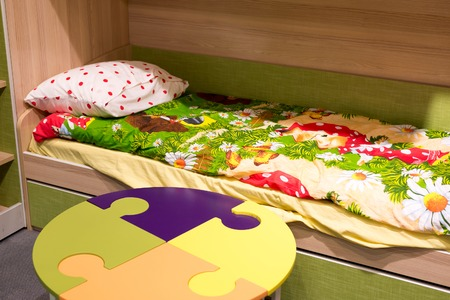 bedstead: Fragment of interior childrens room with a table in the form of a puzzle