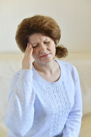 seniors suffering painful illness: Woman holding hands on her head, depression, pain, migraine