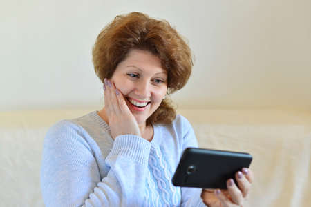 woman on phone: a woman reads SMS on your phone