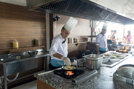 keuken restaurant: ISTANBUL TURKEY SEPT 28 2014 Chef in a restaurant kitchen doing flambe on food Redactioneel