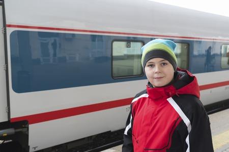 portmanteau: A sad teenager boy standing near train