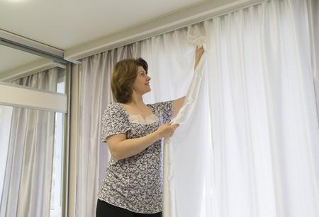 Donna di appendere le tende alla finestra Archivio Fotografico - 49280630