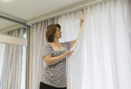 curtain window: Woman hanging up his curtains at the window