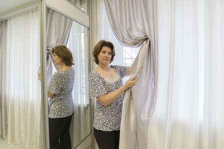 window curtains: Woman caring for curtains hanging in the window