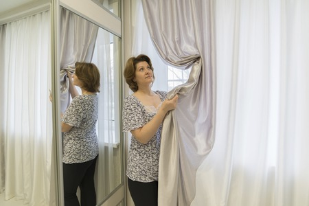caring for: Woman caring for curtains hanging in the window