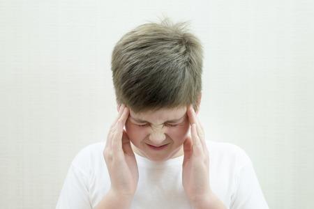 Portrait of a teenage boy with a headache