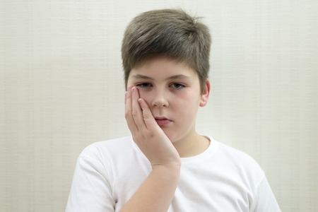 accosting: Teenage boy with a toothache on a light background