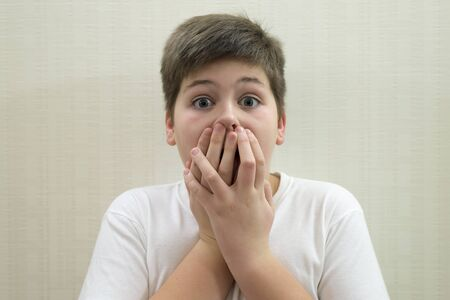 chagrin: Surprised boy closes the mouth with his hands