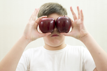 teeny: Portrait of a boy with a red apple in the hand