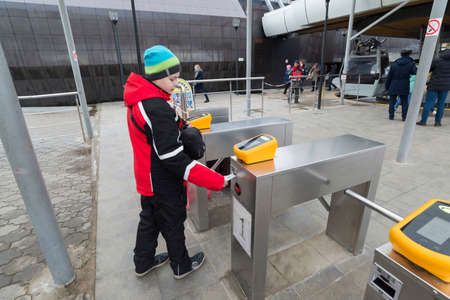 turnstile: Nizhny Novgorod, RUSSIA - November 04.2015. The boy goes through the turnstile cable car. It across the river Volga is the longest in the country