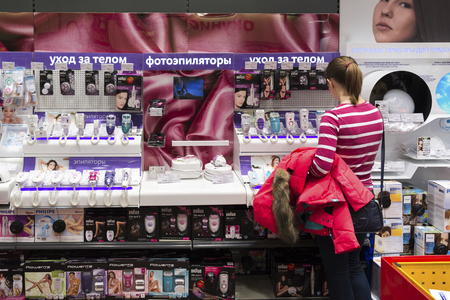 epilator: Khimki, Russia - December 22 2015. Women choose the epilator in Mvideo large chain stores selling electronics and household appliances