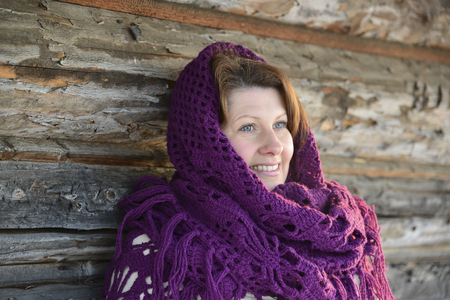 warms: The Russian woman in a shawl warms hands near an izba Stock Photo