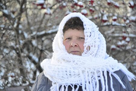 about age: An elderly woman in a white knitted shawl costs about Rowan Stock Photo