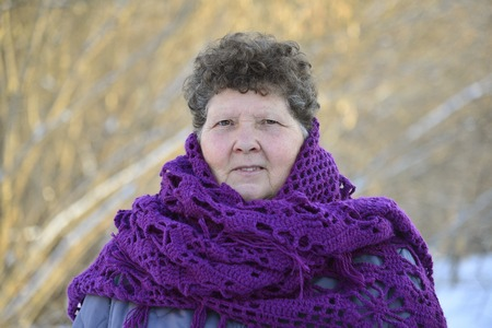 about age: A woman with a purple knitted shawl on his shoulders outdoors in winter