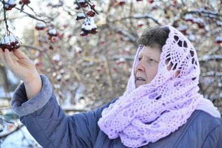 heats: Elderly woman in a lilac knitted scarf on her head outdoors