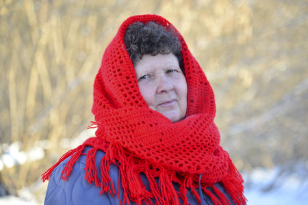 heats: Elderly woman in a redknitted scarf on her head outdoors