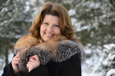 middleaged: Positive middle-aged woman in a winter forest Stock Photo