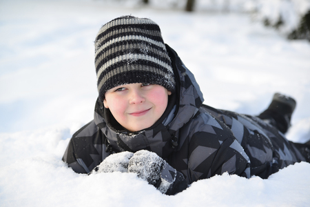 lies: Teen boy lies in the snow in the winter forest Stock Photo