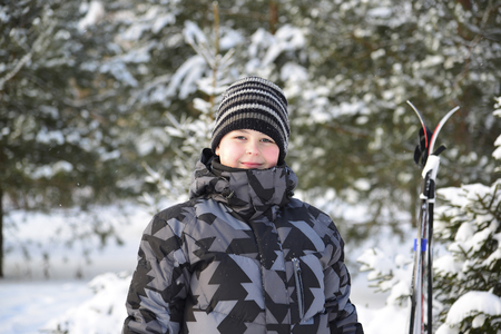 soundness: Teen Boy with skis in a pine forest in winter