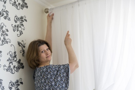 white curtains: Woman hanging up his white curtains at the window