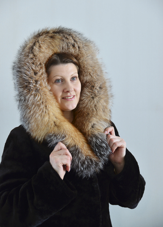 cowl: A woman in a fur coat on a light background