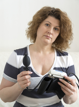 therapeutics: An adult woman holding automatic tonometer for measuring blood pressure Stock Photo