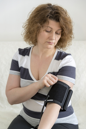 therapeutics: woman checking her blood pressure by tonometer.