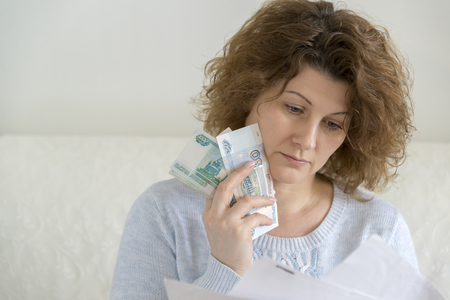 exasperation: An adult woman with receipts and Russian money Stock Photo