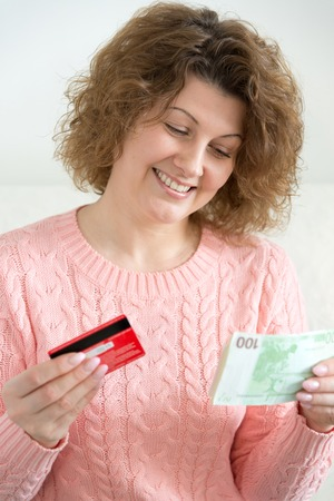 woman holding money: An adult woman holding money and credit cards