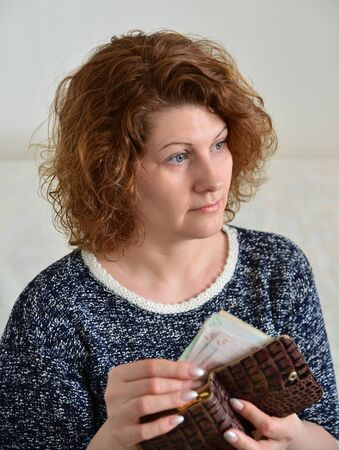 rubles: A thoughtful Russian woman pulls from her purse rubles