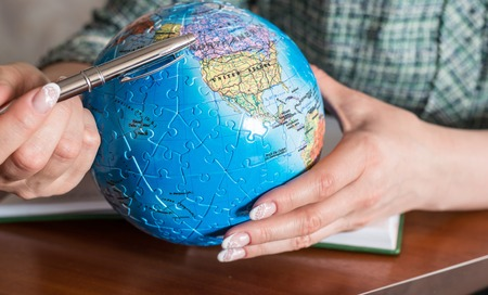 globe puzzle: Female hand with a pen and a globe of the puzzle Stock Photo