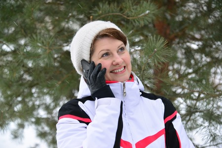rugged terrain: Sport woman talking on the phone in a pine forest in winter Stock Photo