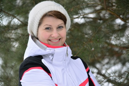 deep powder snow: A woman in a sports jacket and hat in a pine forest in winter