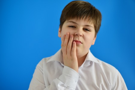 accosting: Teenage boy with a toothache on light background