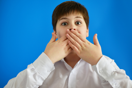 Surprised boy closes the mouth with hands Stockfoto
