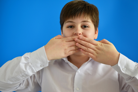 teener: Surprised boy closes the mouth with hands Stock Photo